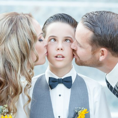 Bride and Groom Kiss Son Before Ceremony