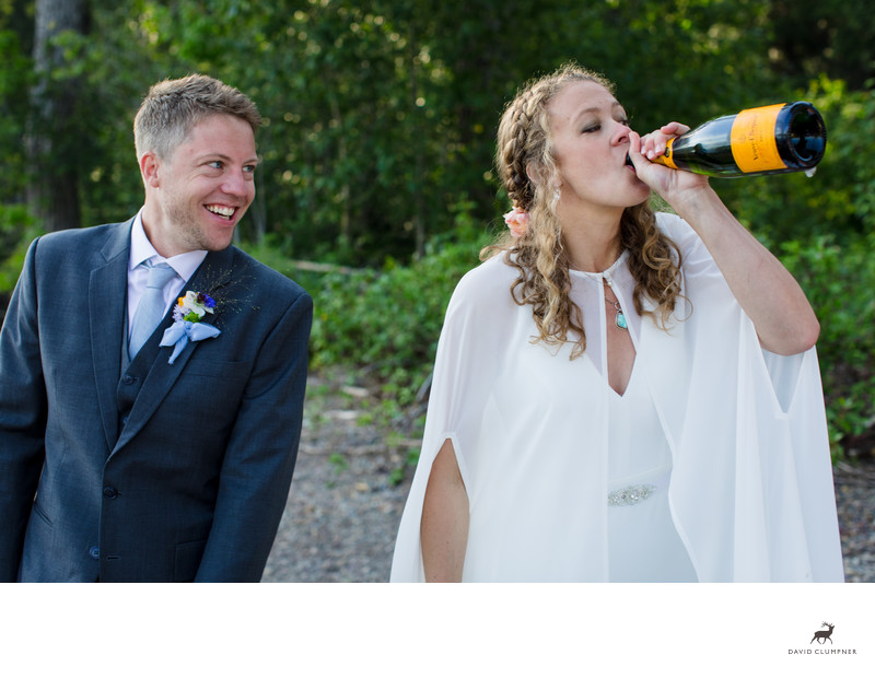 Bride Drinking Directly from Bottle of Champagne