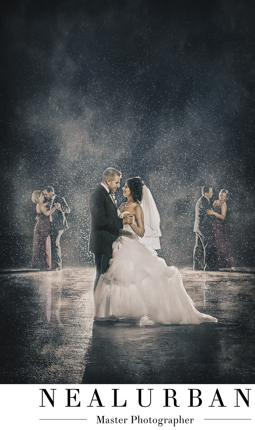 Bride and groom dance in the rain with wedding party antonios in niagara falls