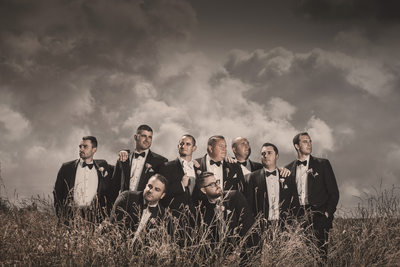 groomsmen buffalo country wedding pose field in tuxes