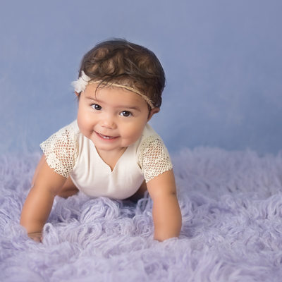 Smiling baby girl on purple rug