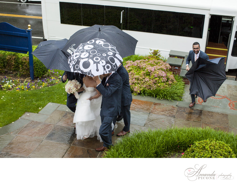 Bride with umbrellas in rain before wedding ceremony