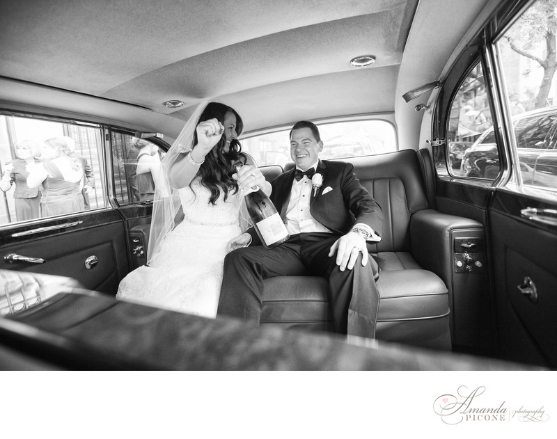 Bride and groom pop champagne in limo NYC wedding