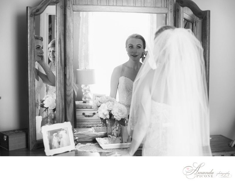 Bride in mirror as mom looks on preparing for wedding