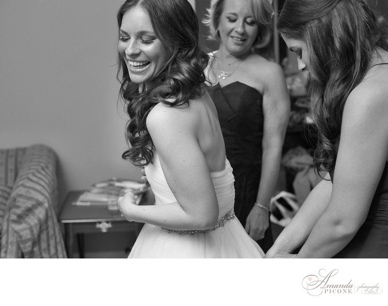 Bride laughs getting into dress before ceremony