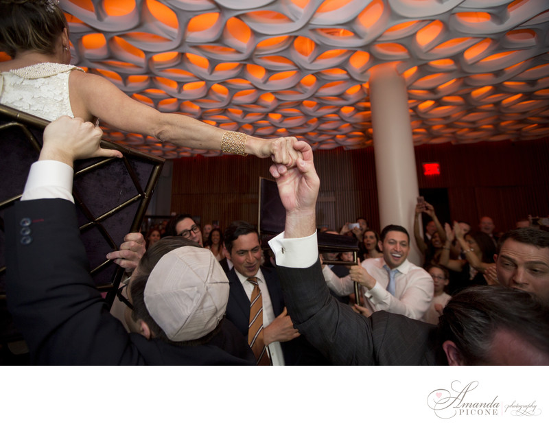Bride and groom hold hands during hora Trump SoHo