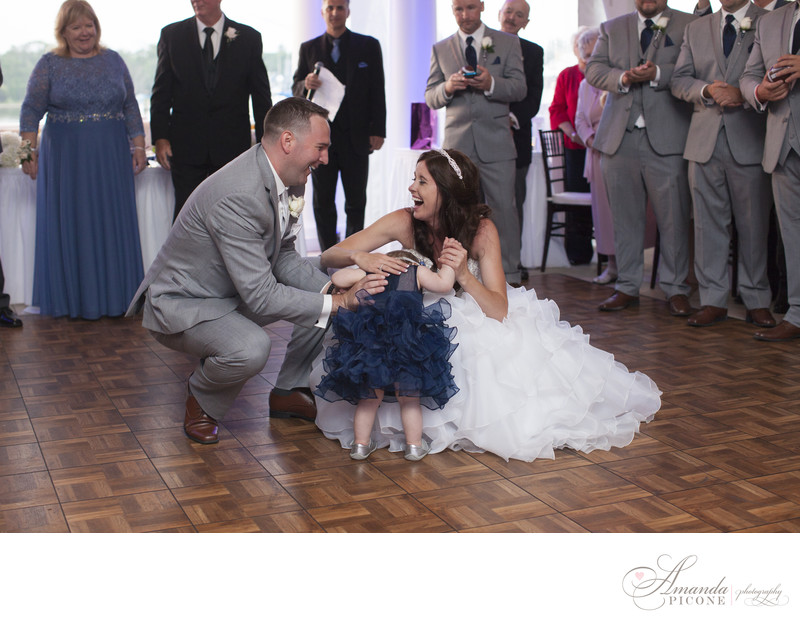 Bride and groom first dance with daughter at wedding