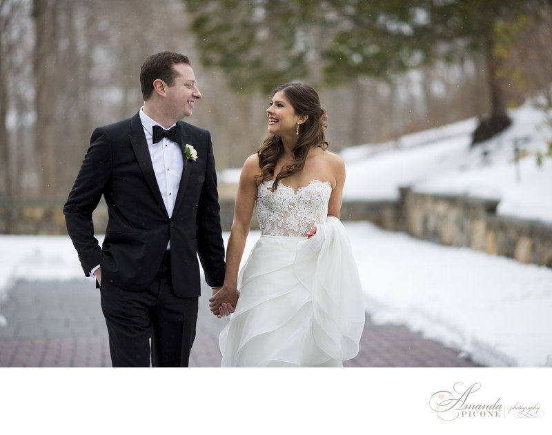 Bride and groom walking in snow at Tappan Hill Mansion