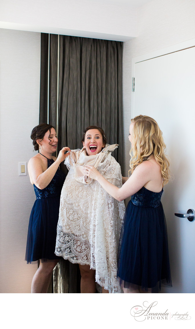 Bride gets into wedding gown with bridesmaids