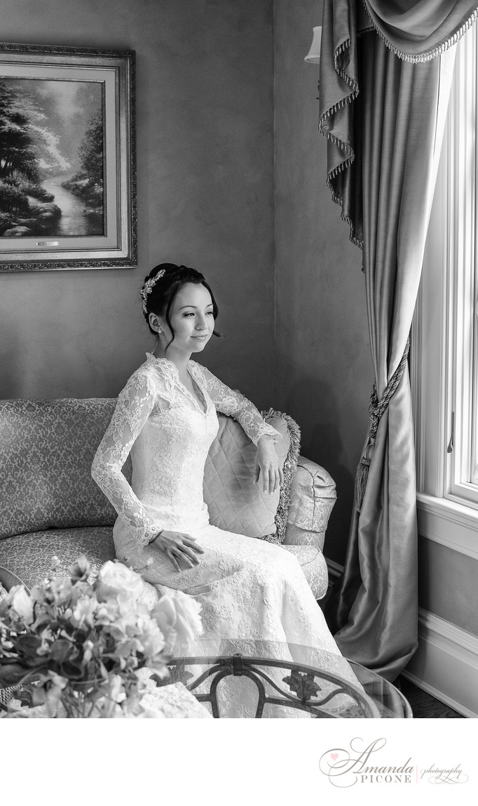 Bride looking out window in wedding gown