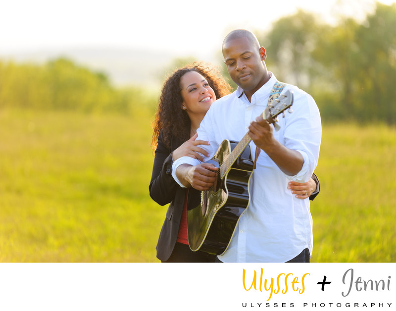 Engaged couple in field playing guitar