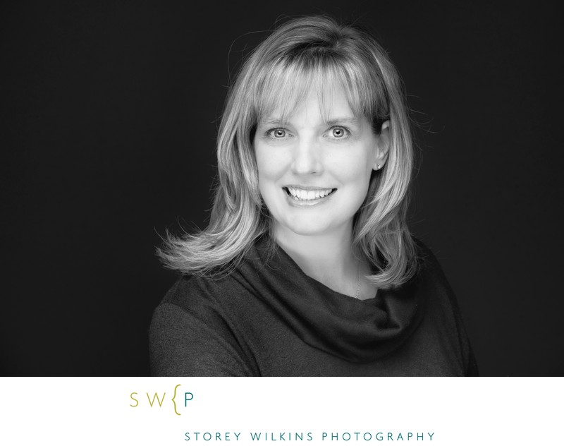 Black and white corporate headshot with feminine pose