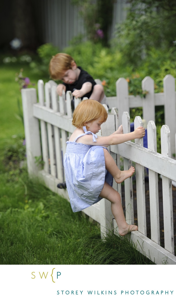 Brother and Sister Climbing Fences