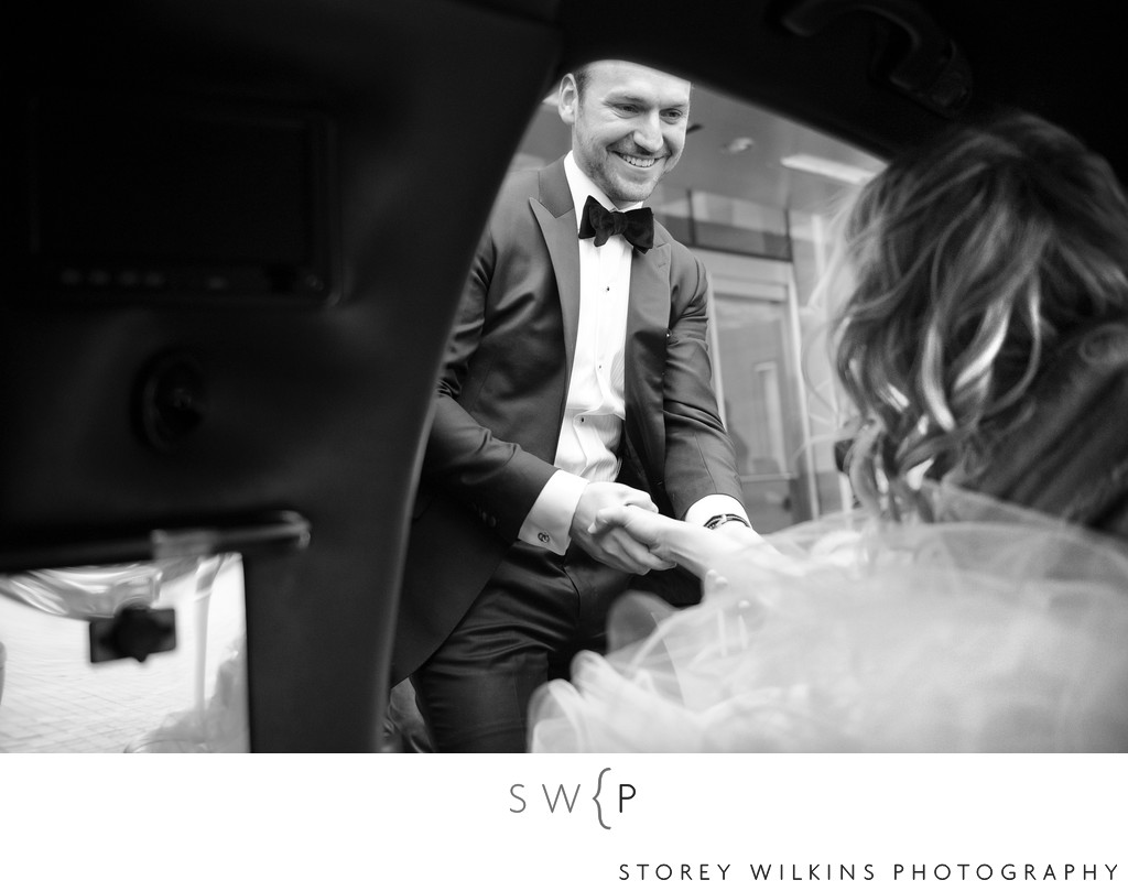 Groom Helps Bride from Car as they Arrive at Reception