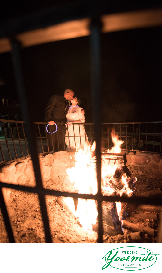 Bride And Groom Kiss Behind Fire Pit At Tenaya Lodge