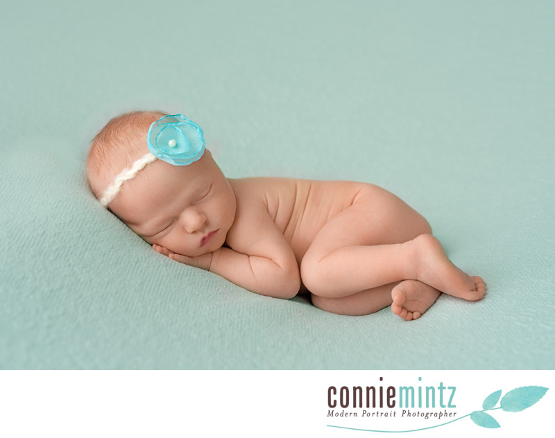 posed newborn on a mint green blanket