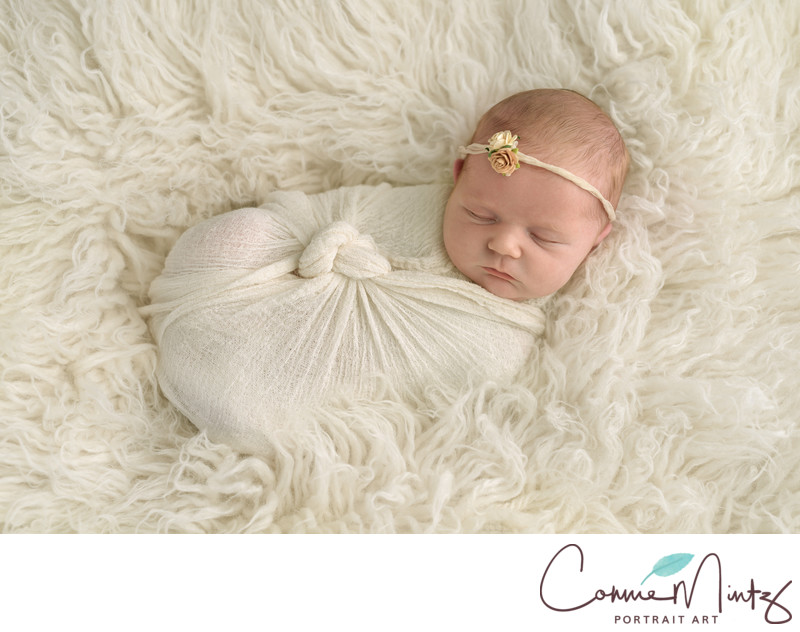 Newborn in cream wrap on flokati rug