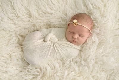 Newborn In Cream Wrap On Flokati Rug