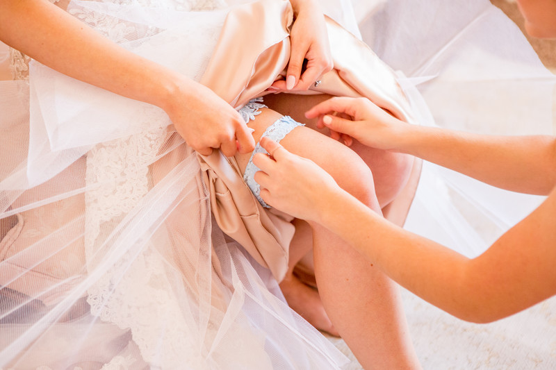 Bride putting on garter Phoenix Wedding Photographer
