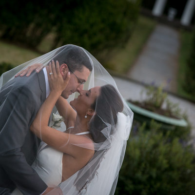 Groom Embraces Bride Under The Veil In A Courtyard