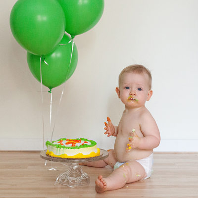 Baby digs into cake with green balloons