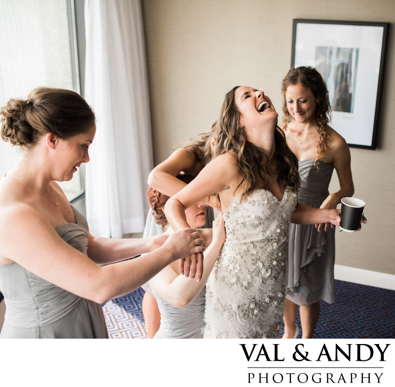 Bridal Party help bride into wedding dress laughing