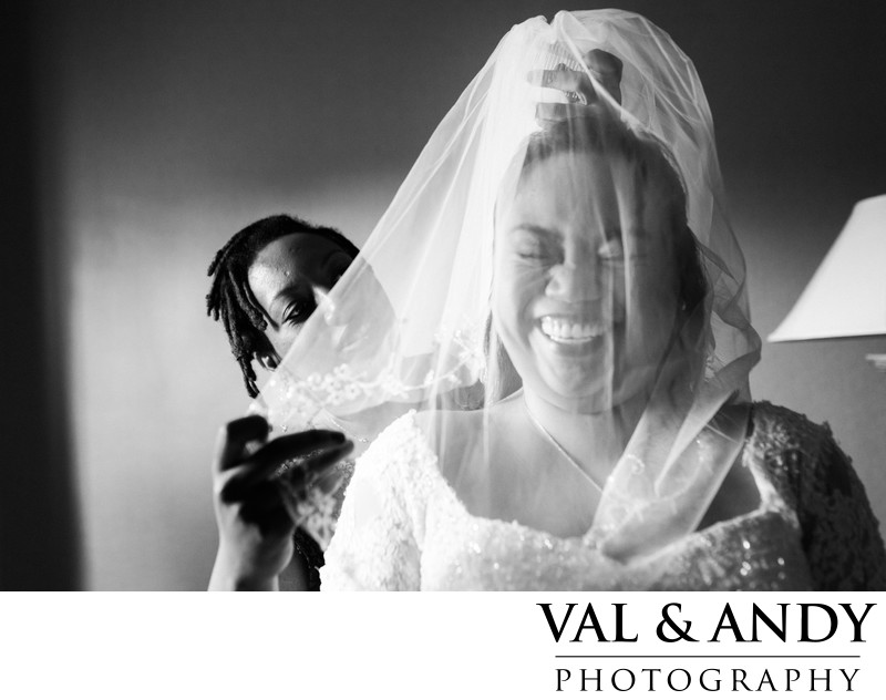 Maid of Honor help the laughing bride but veil on