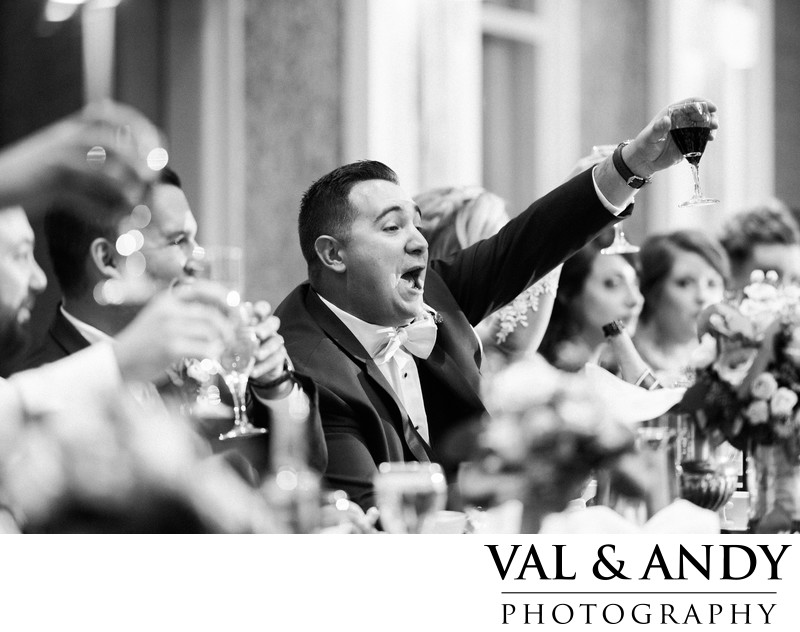 Energetic Groom raises glass for toast