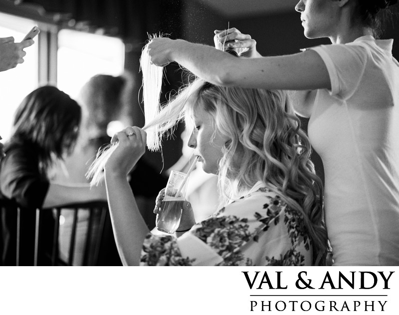 Bride getting ready with a drink while holding her hair