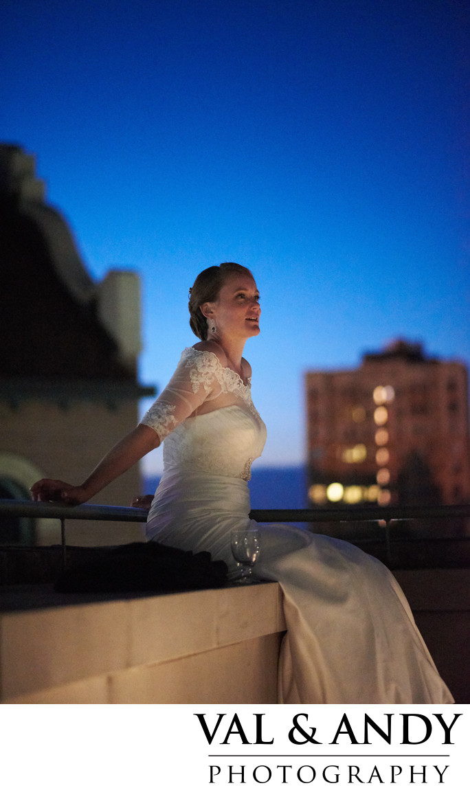 Bride on a ledge viewing her reception after a long day