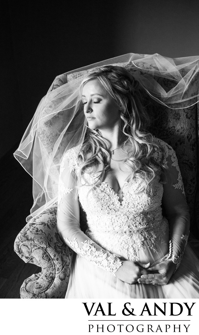 Elegant Bride sits in Chair by window light with vail