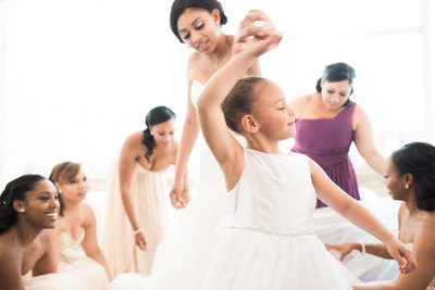 Bride spins flower girl while dancing with bridesmaids