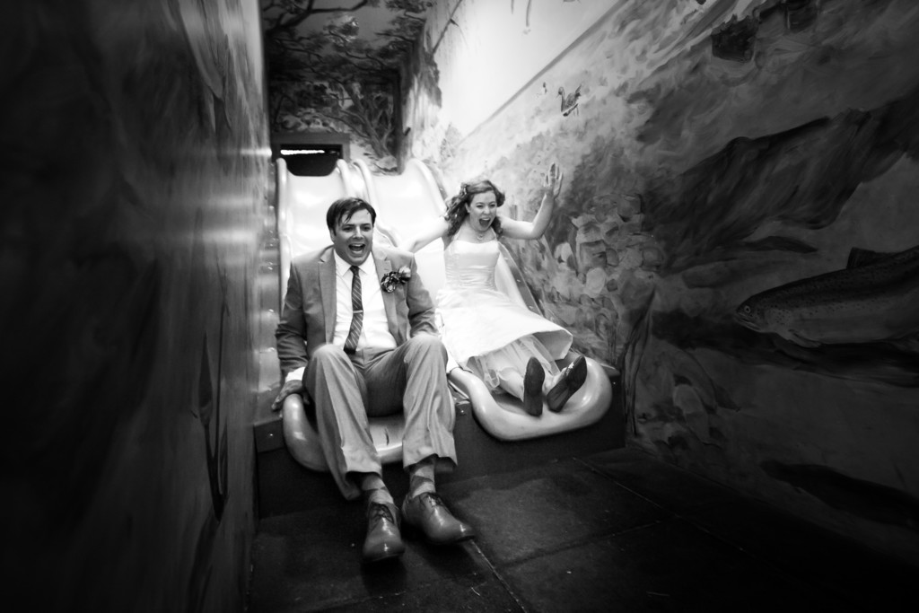 bride and groom on a slide at Urban Ecology Center