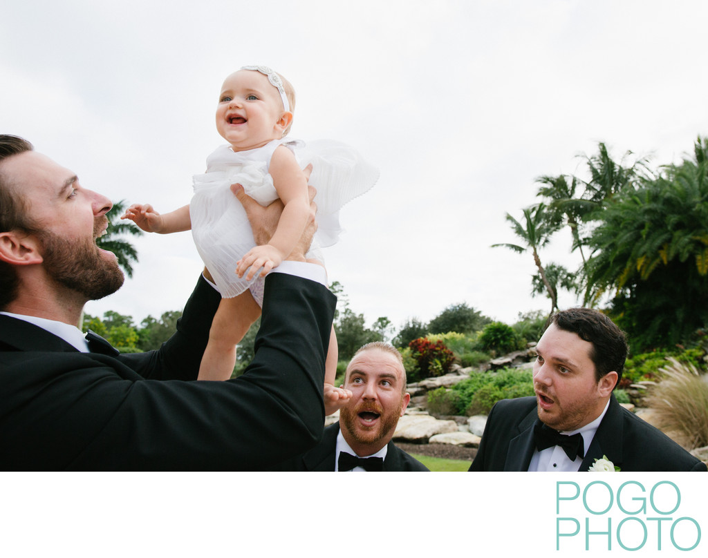 Groomsmen being silly with flower girl during formals