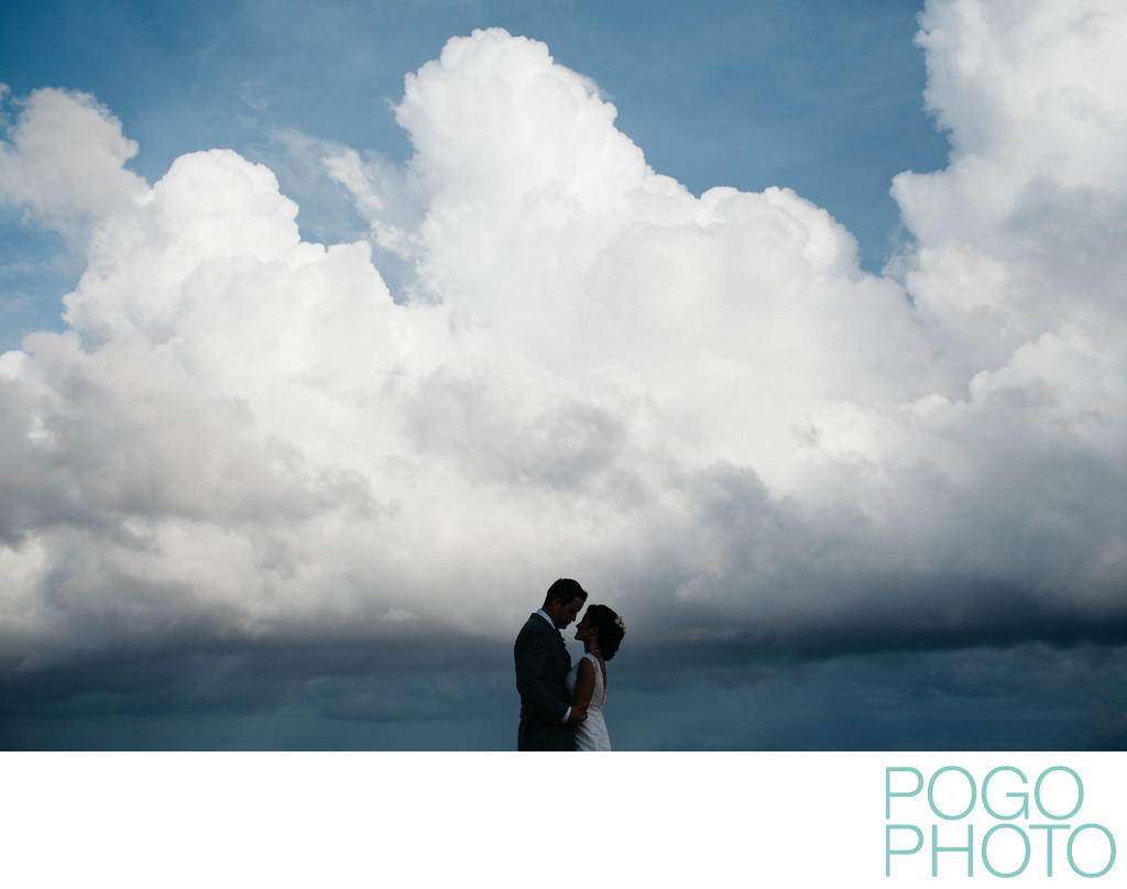 Silhouetted wedding portrait against dramatic clouds