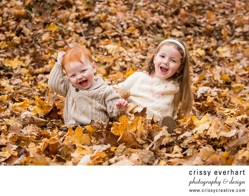 Fall portraits kids laughing in the leaves