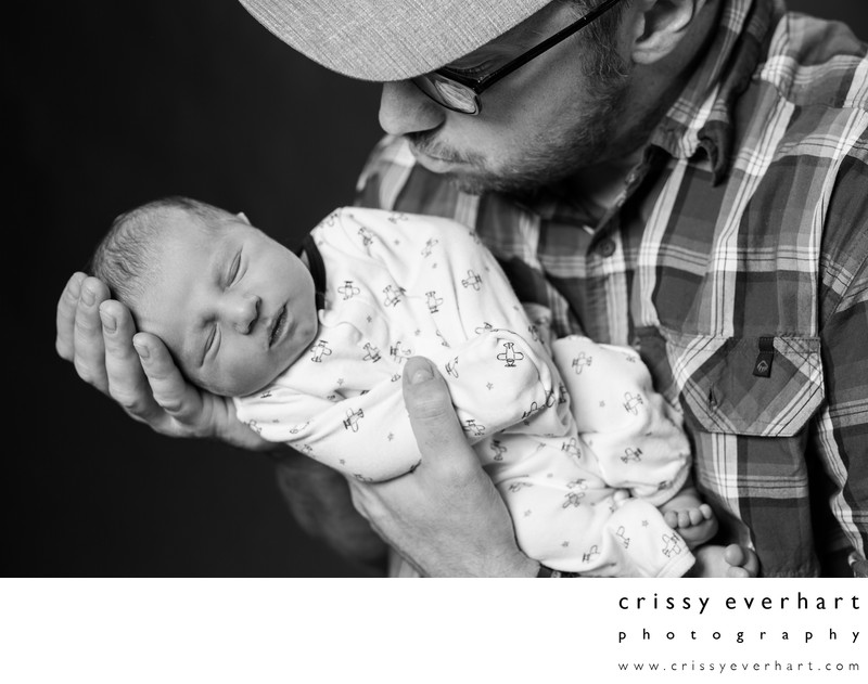 Dad Holds Son in Hands- Newborn Photographer in Malvern