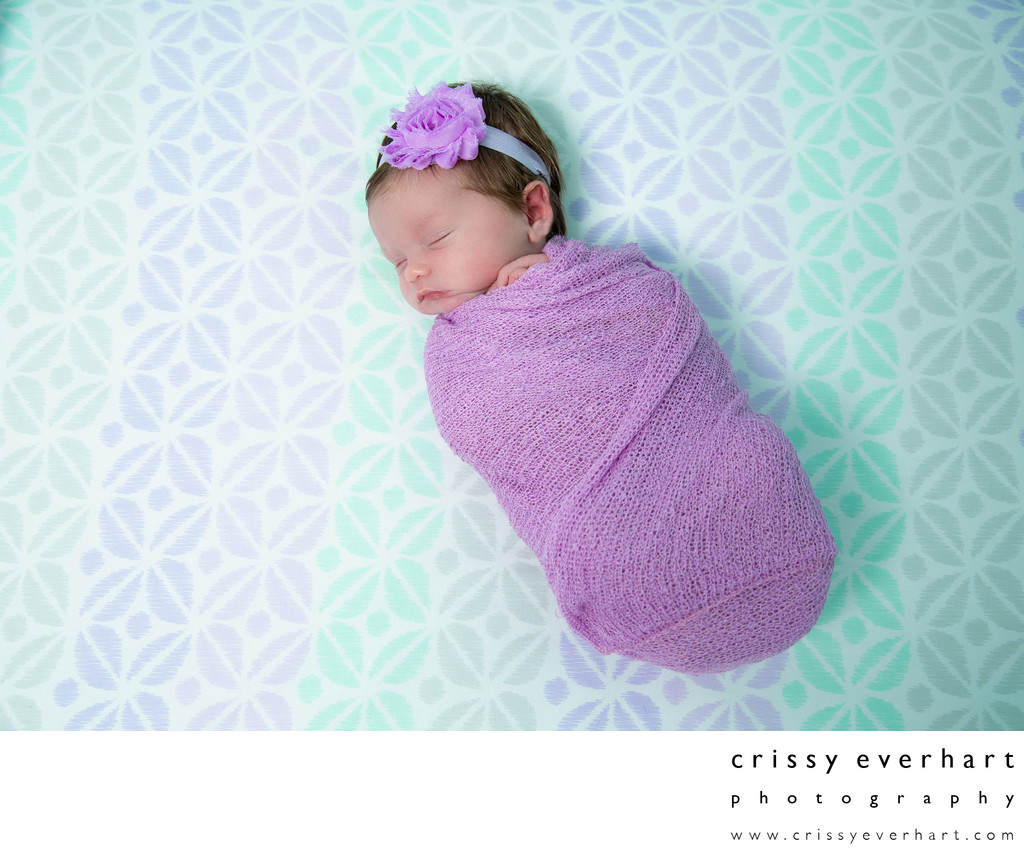Swaddled Newborn in Crib, Purple and Teal