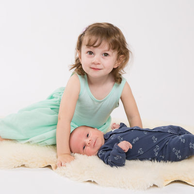 New Big Sister Leans Over Newborn Brother