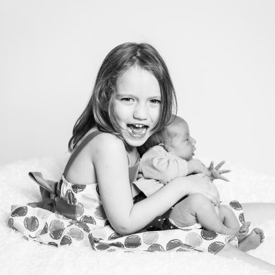 Excited Big Sister Holds Newborn Little Sis