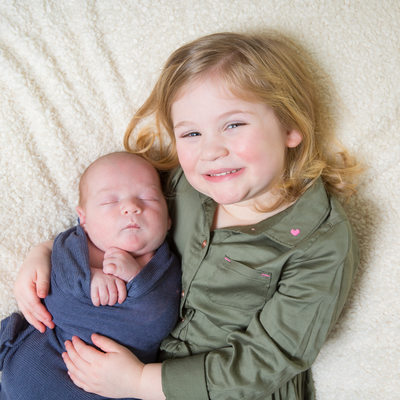Proud Big Sister Holds Newborn Baby Brother