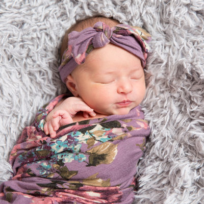 Sleeping baby girl in purple flowered swaddle