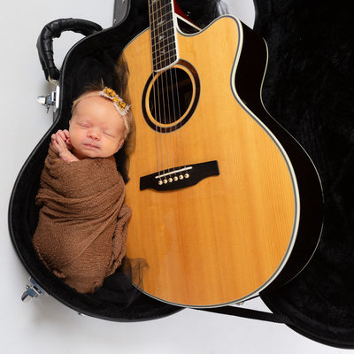 Swaddled Newborn Baby Girl in Guitar Case