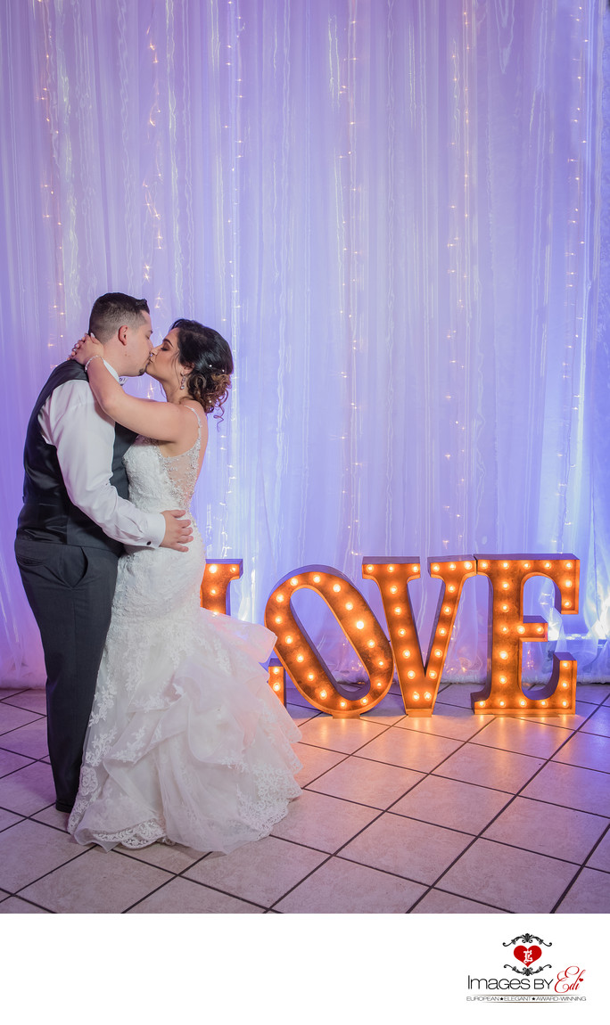 The Grove wedding reception kiss by the LOVE sign