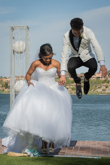 Reflection Bay Las Vegas Wedding Photography | Vegas Wedding Photos | Groom Jumping Over the Broom During Reflection Bay Las Vegas Wedding Ceremony | Images by EDI