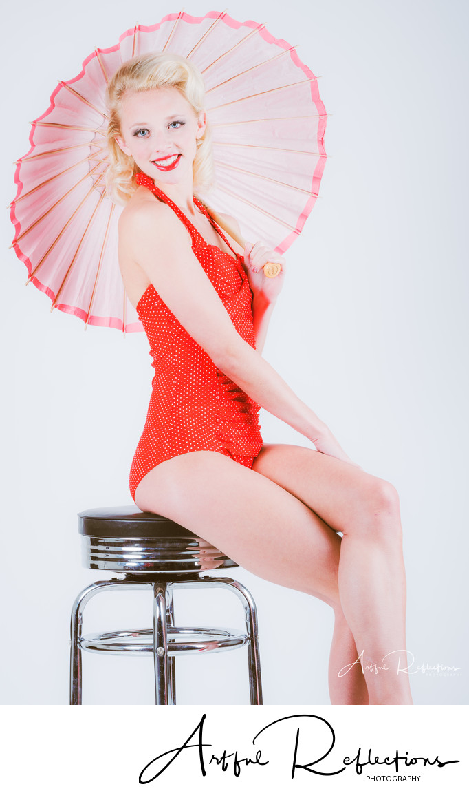 Pin-up model sitting on bar stool with umbrella