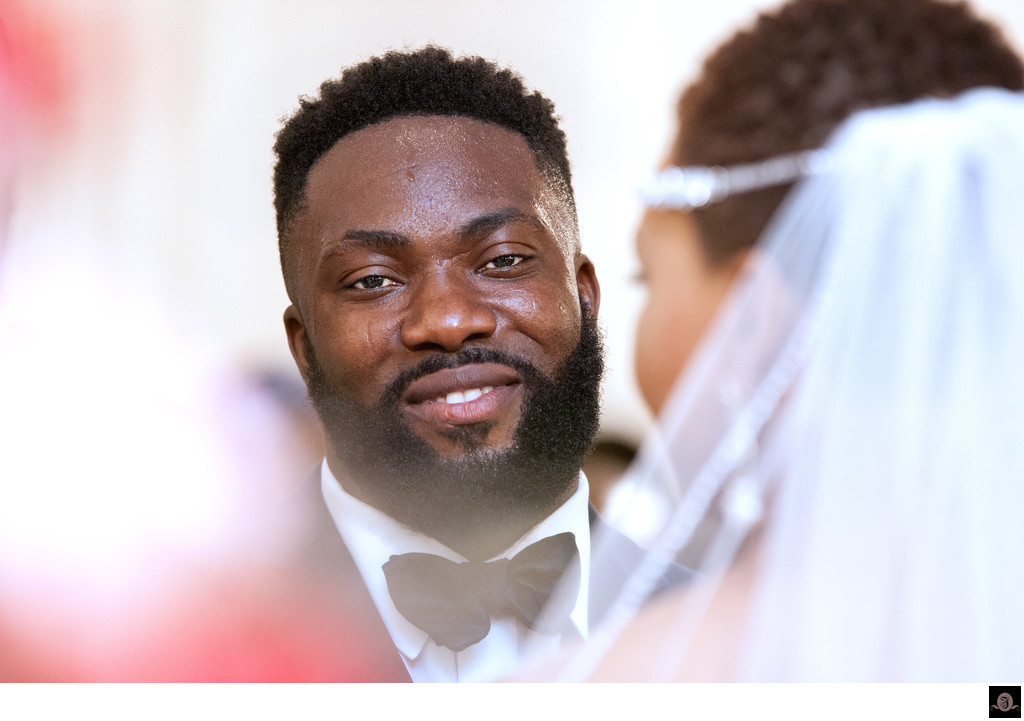 Perspiring groom smiles during the wedding ceremony