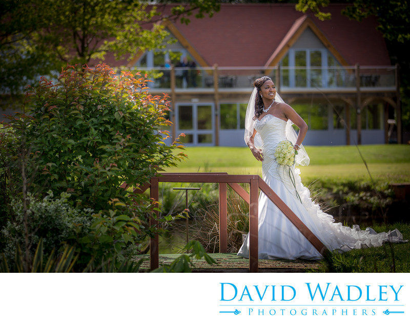 Bride on bridge with clubhouse at Nailcote Hall.