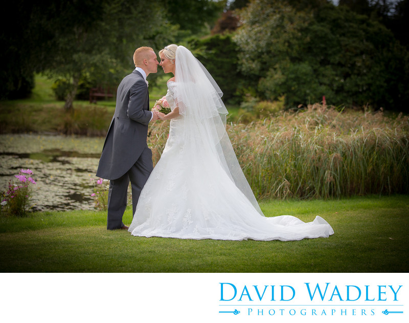 Kissing the bride in the lovely gardens of Nailcote Hall.