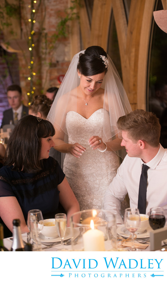 Bride photographed with wedding guests at Shustoke Barn.